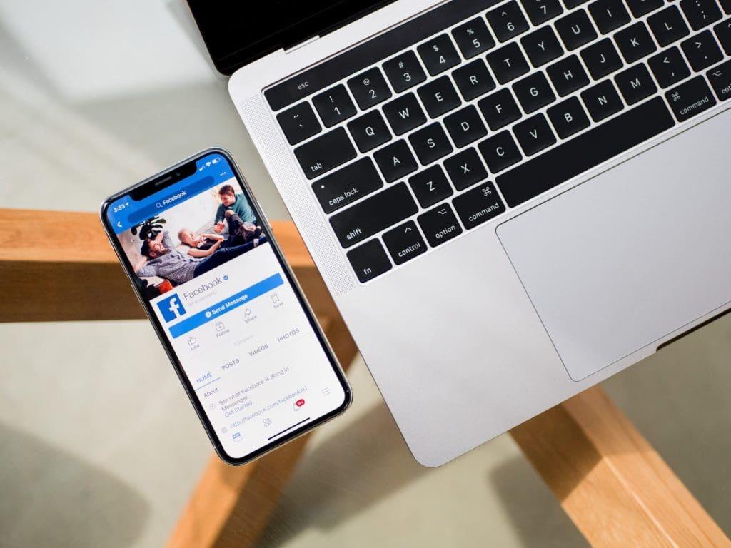 Net Reputation - Facebook on phone next to laptop