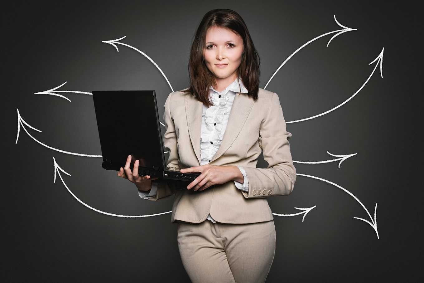 businesswoman holding laptop with arrows in background