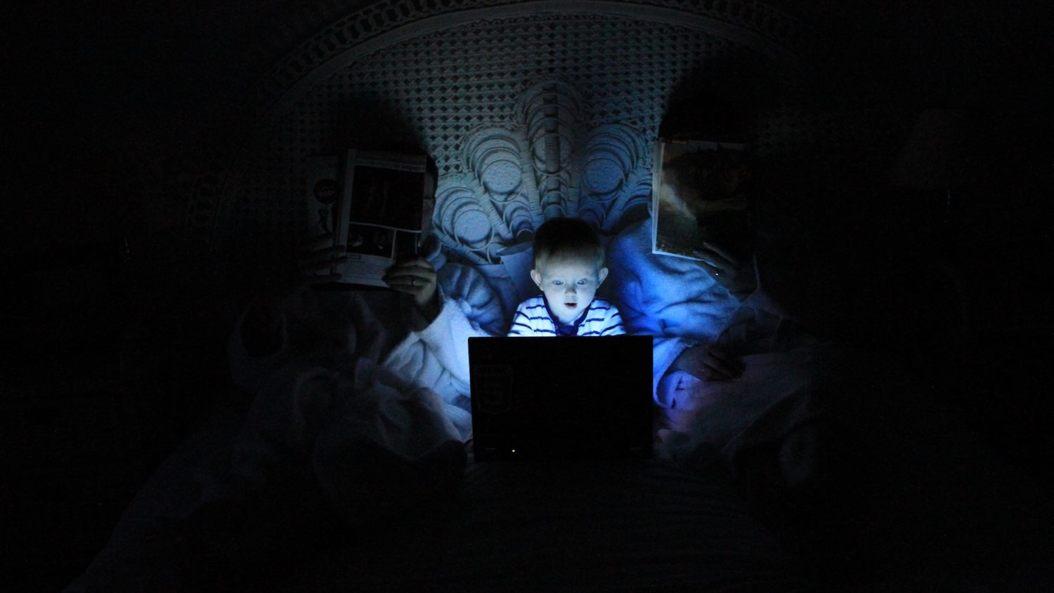 young boy in bed looking at laptop in the dark