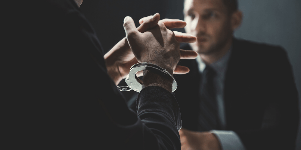 person in handcuff in meeting with lawyer