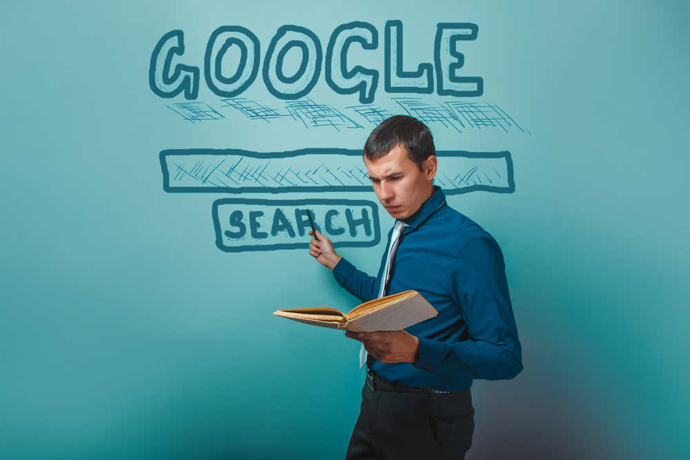 male creating google search on blue board